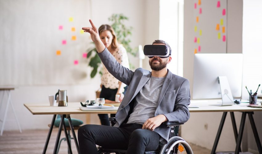 Two business people with wheelchair in the office working together. A man wearing VR goggles.